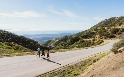 three runners running together downhill