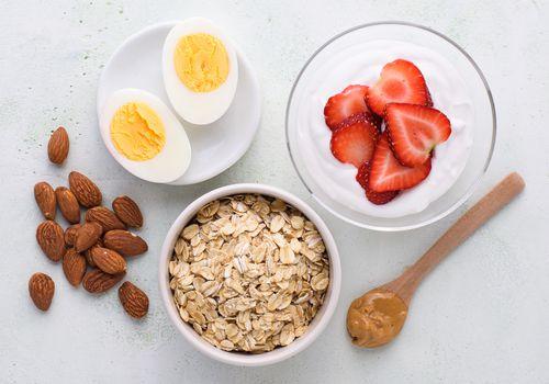 alimentos para comer antes de una carrera que incluyen avena, mantequilla de maní, almendras, huevos duros y yogur con fruta