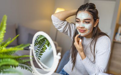 woman applying a face mask at home