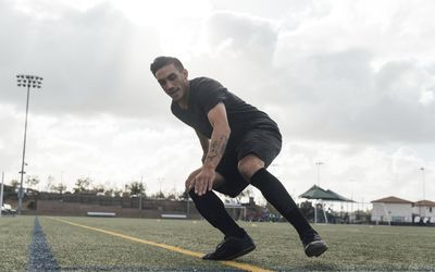 Soccer players performing warm up drills on field