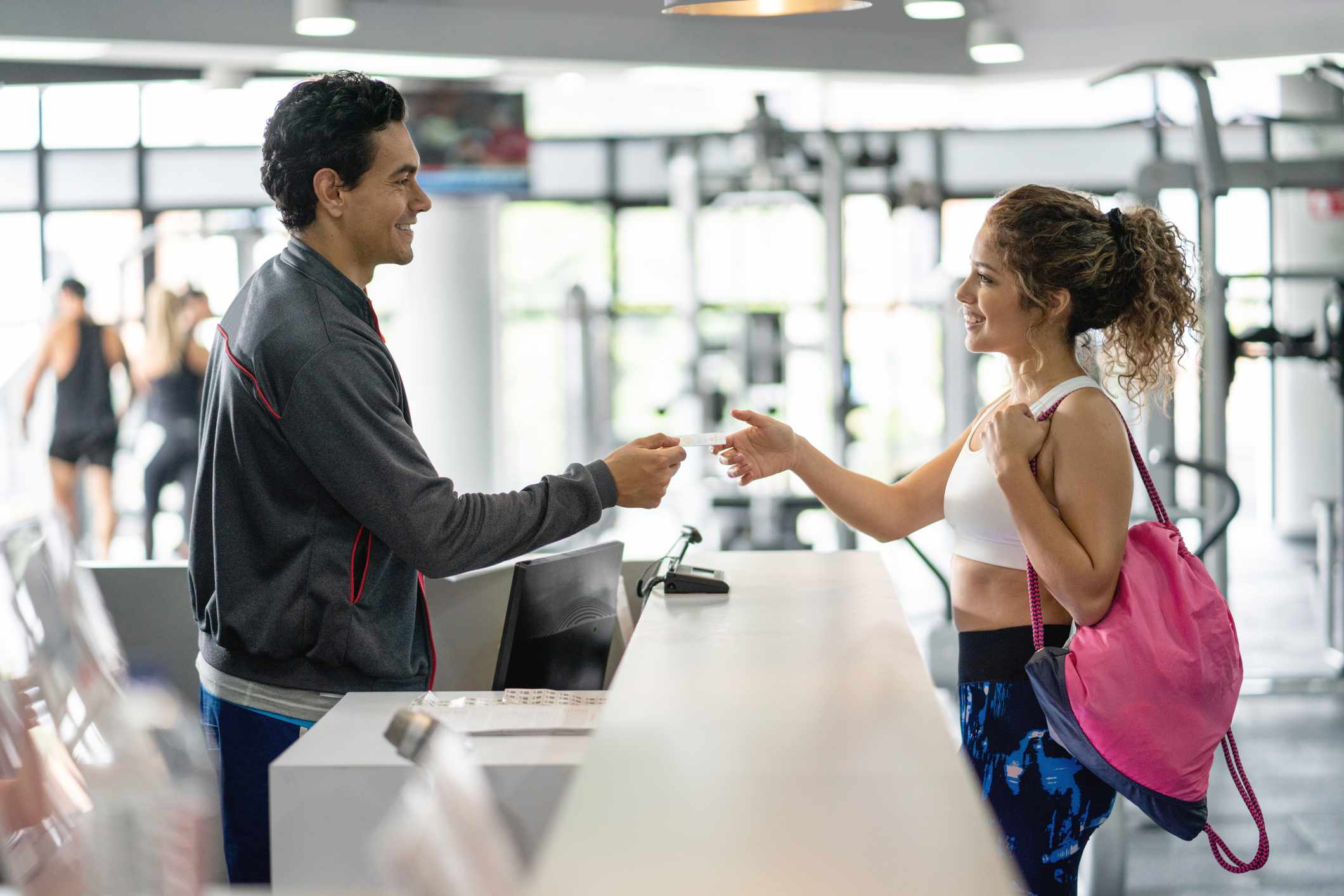 Cheerful employee at the gym handing a membership card to beautiful female customer