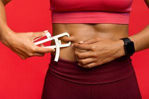 Woman measuring her body fat with body fat caliper