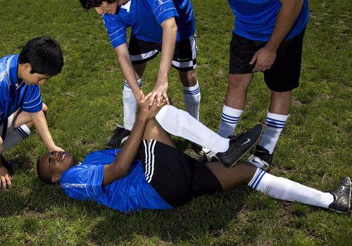 Jugador de fútbol en el campo con dolor en la rodilla