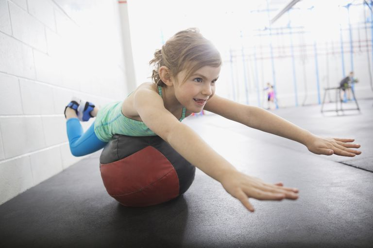 Girl balancing on medicine ball