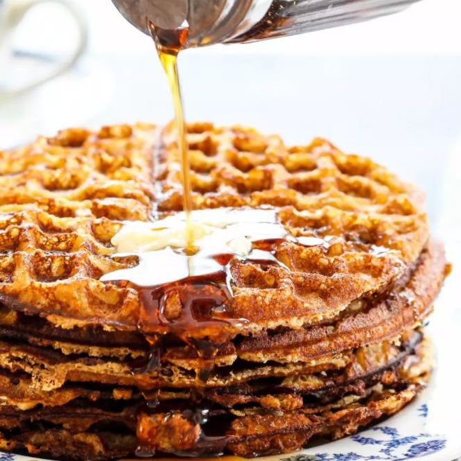 Maple syrup pouring onto crispy waffles