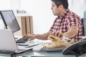 Businessman eating and working at desk