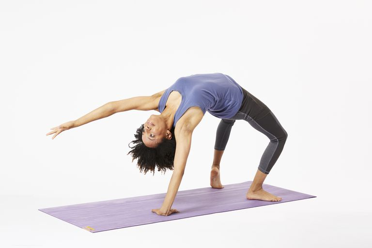 Woman on yoga mat doing wild thing pose