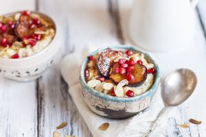 Porridge with cinnamon, millet, backed plum, pomegranate and roasted almond slivers