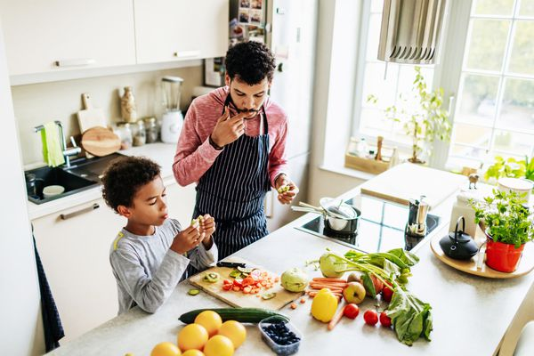 Man and son in a kitchen cooking and slicing fruits and vegetables.