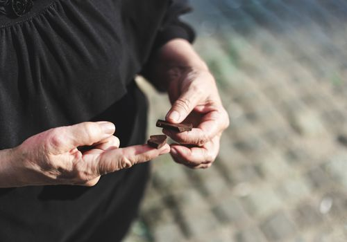 hands of older woman eating chocolate