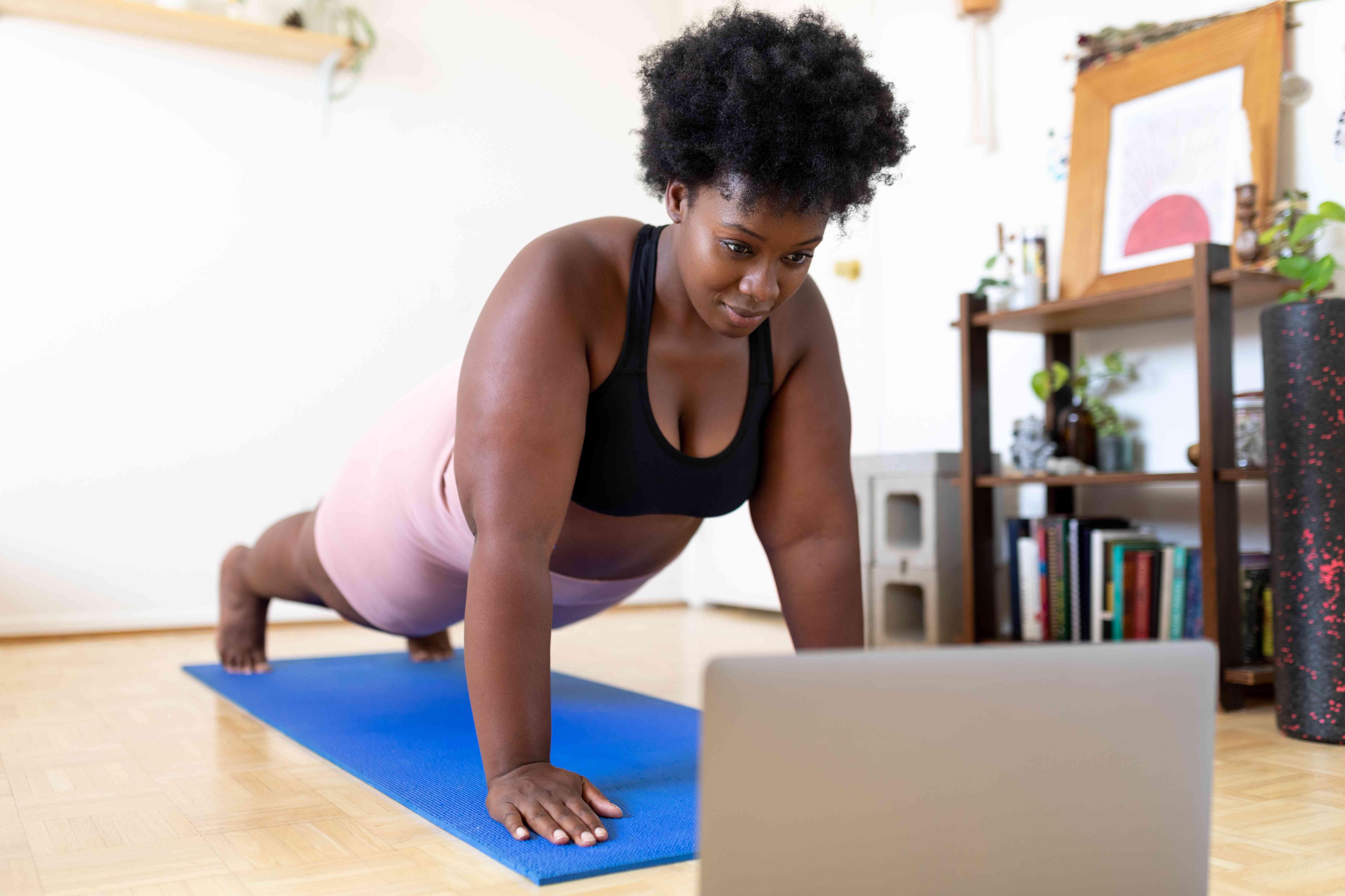 Woman doing mat Pilates at home following a fitness video online