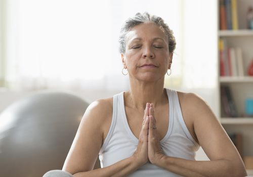 Older Hispanic woman meditating in living room