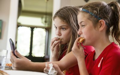 little girls taking a selfie of them eating food