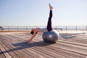 Woman stretching on exercise ball on promenade