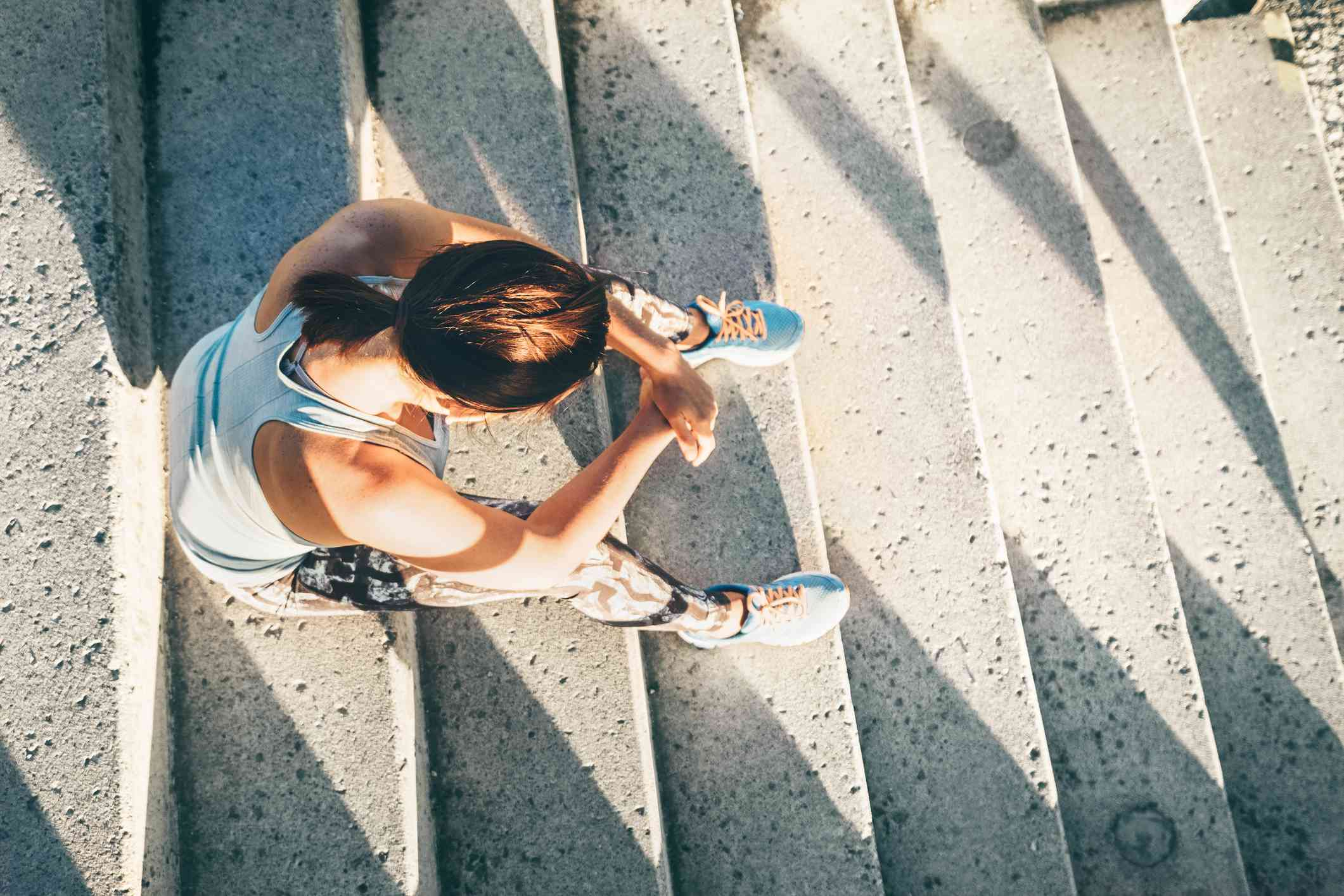 Woman rests on stairs after a run