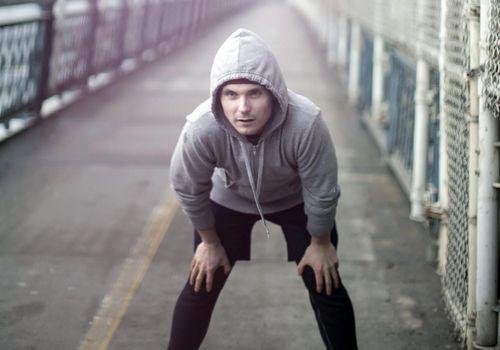 Corredor con la mano sobre las rodillas en un camino de carrera