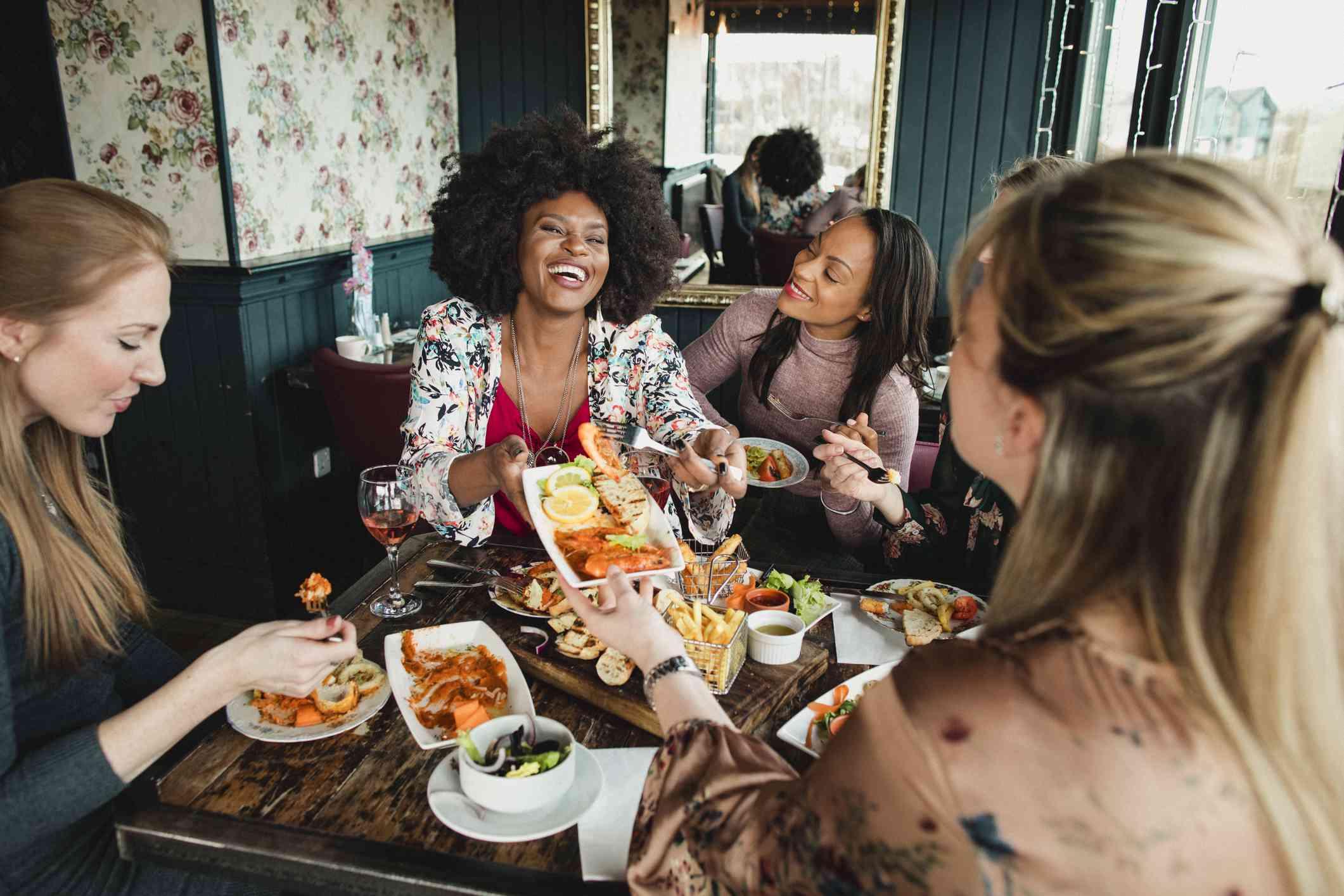 Grupo de mujeres comiendo y hablando en un restaurante