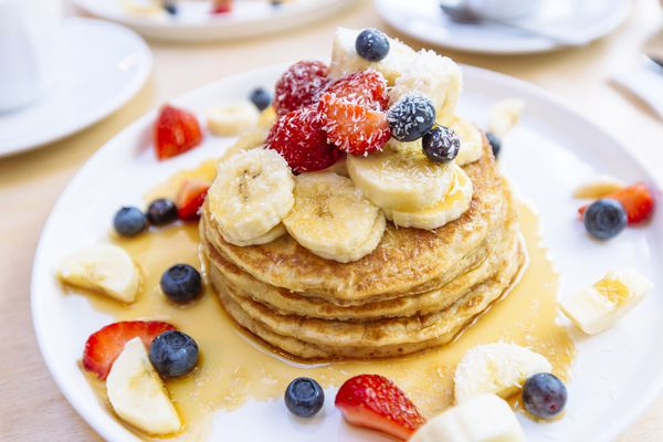 Stack of whole grain pancakes topped with fruit
