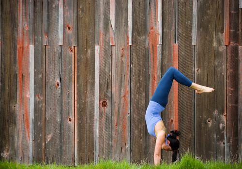Mujer haciendo yoga invertido plantean fuera