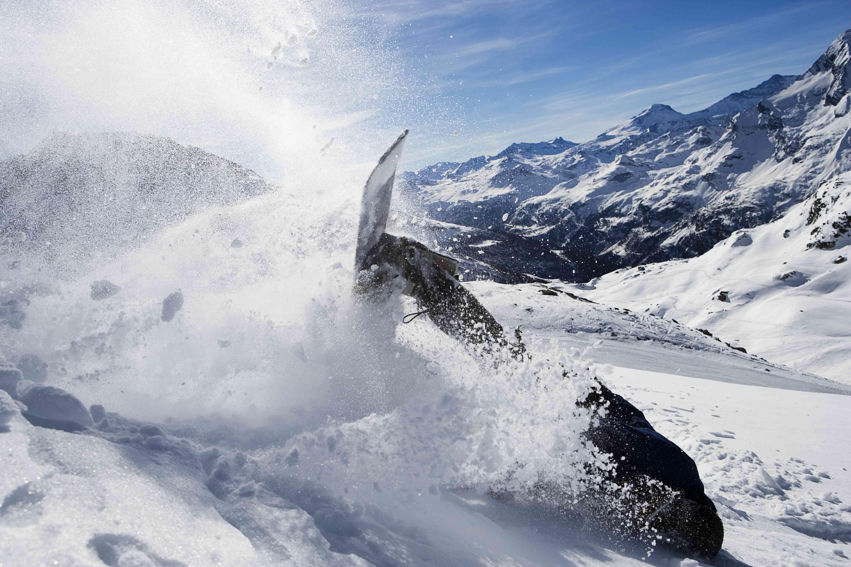 Snowboarder masculino cayendo en la montaña