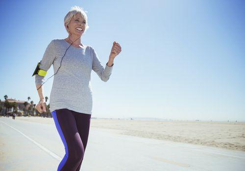 Senior woman jogging on beach boardwalk