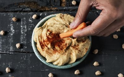 Person eating carrots and hummus