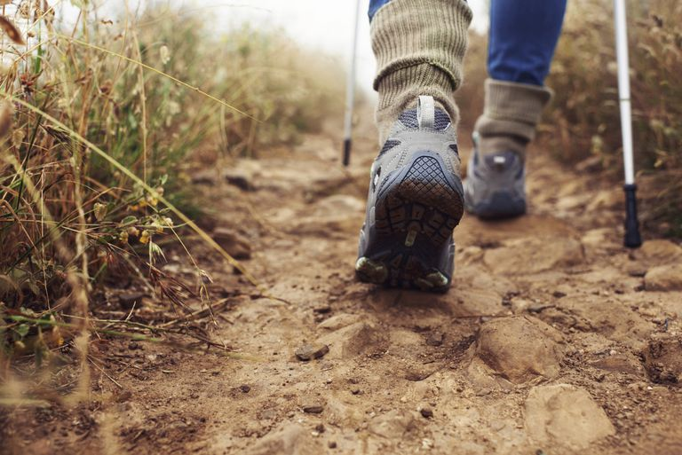 close-up of person's feet wearing hiking shoes and walking on dirt path