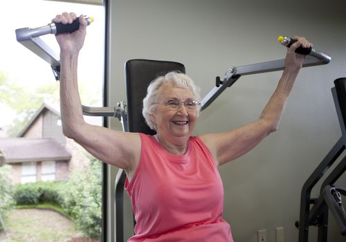 An elderly woman using a strength machine in a gym