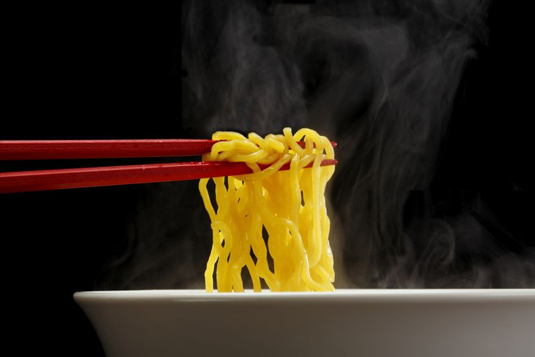 Red chopsticks picking up ramen