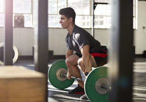 A male weightlifter sets up for a power clean.