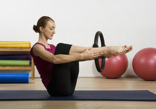 Mujer sentada sobre una estera, usando un círculo de Pilates