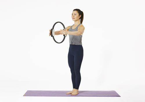 Mujer de pie sobre una estera de yoga con Pilates Magic Circle