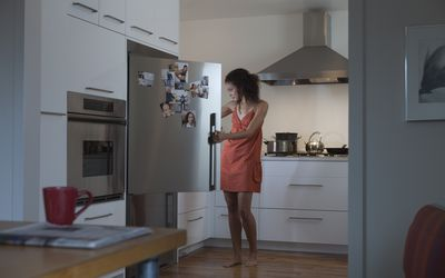 Woman looking in the fridge in the evening
