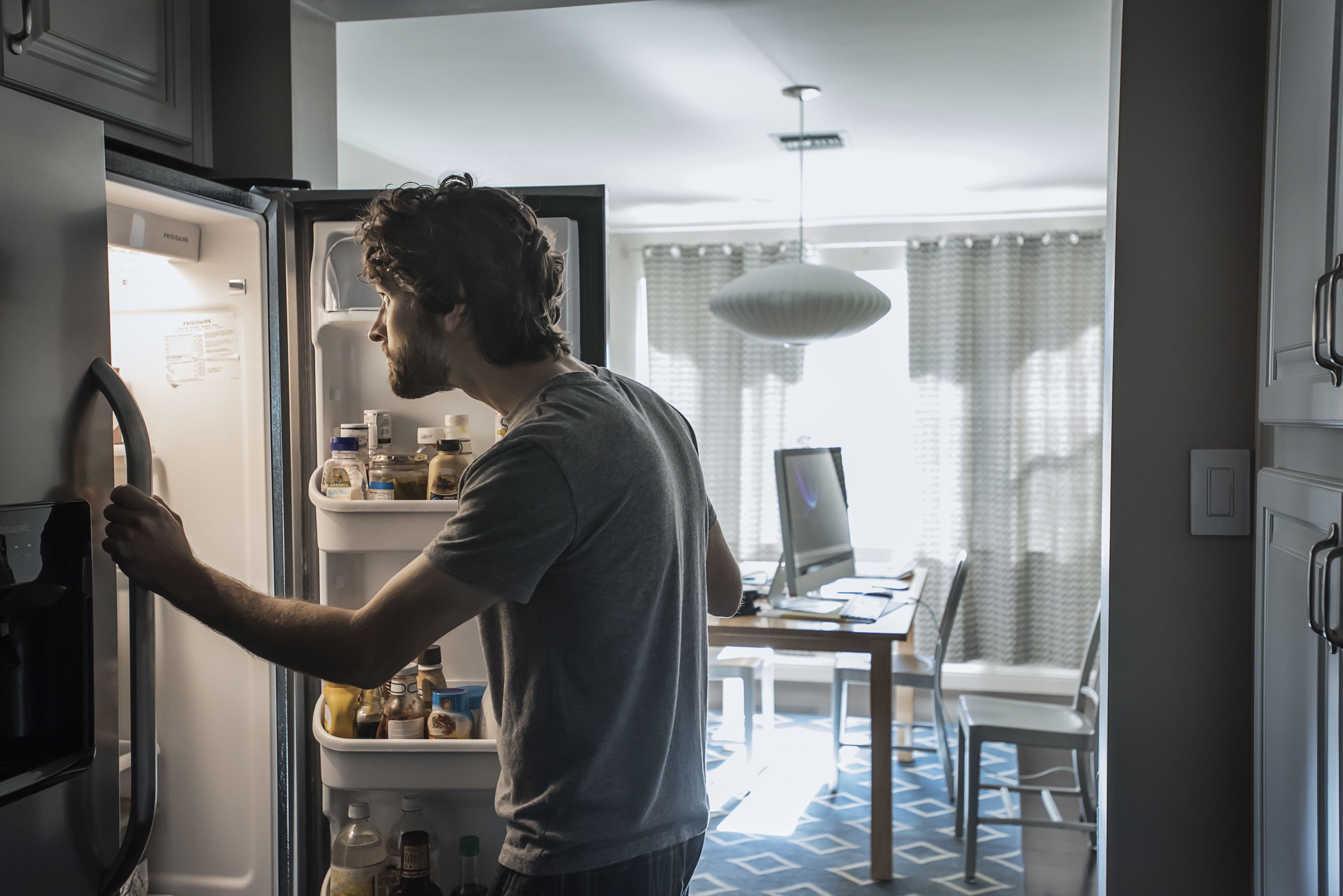 Man checks refrigerator