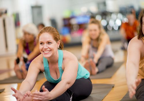 Women in yoga class doing forward fold