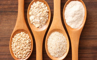 wooden spoons that contain various types of oats, including oat flour