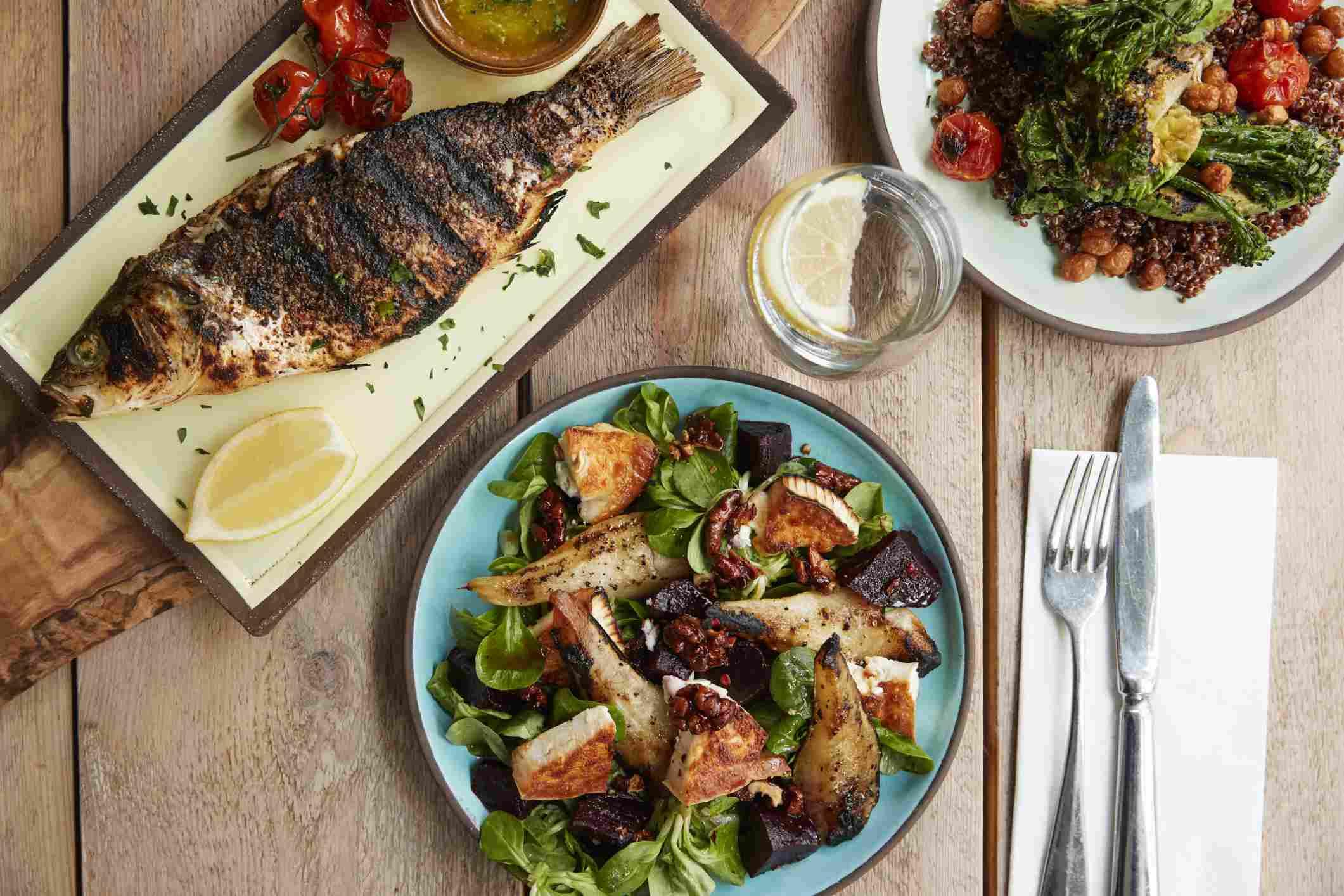 Tabla de dieta mediterránea con pescado, ensalada y verduras.