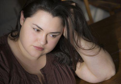Mujer con sobrepeso sumida en sus pensamientos
