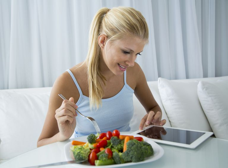 woman eating vegetables and checking iPad