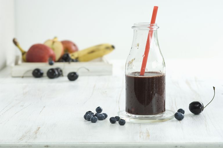 Smoothie, superfood, cherry, banana, blueberry, apple smoothie in bottle  with drinking