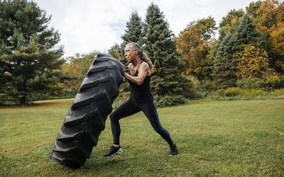 woman flipping a tire for exercise outdoors