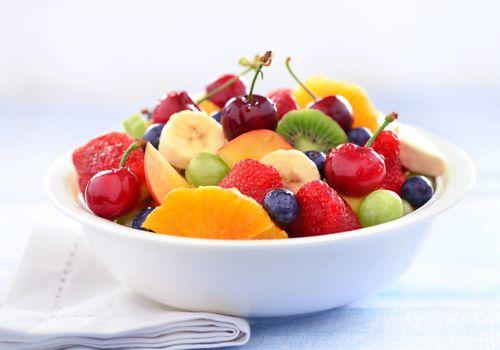 Un plato blanco de fruta que contiene rodajas de naranjas, cerezas, kiwi, fresas, uvas y plátanos.
