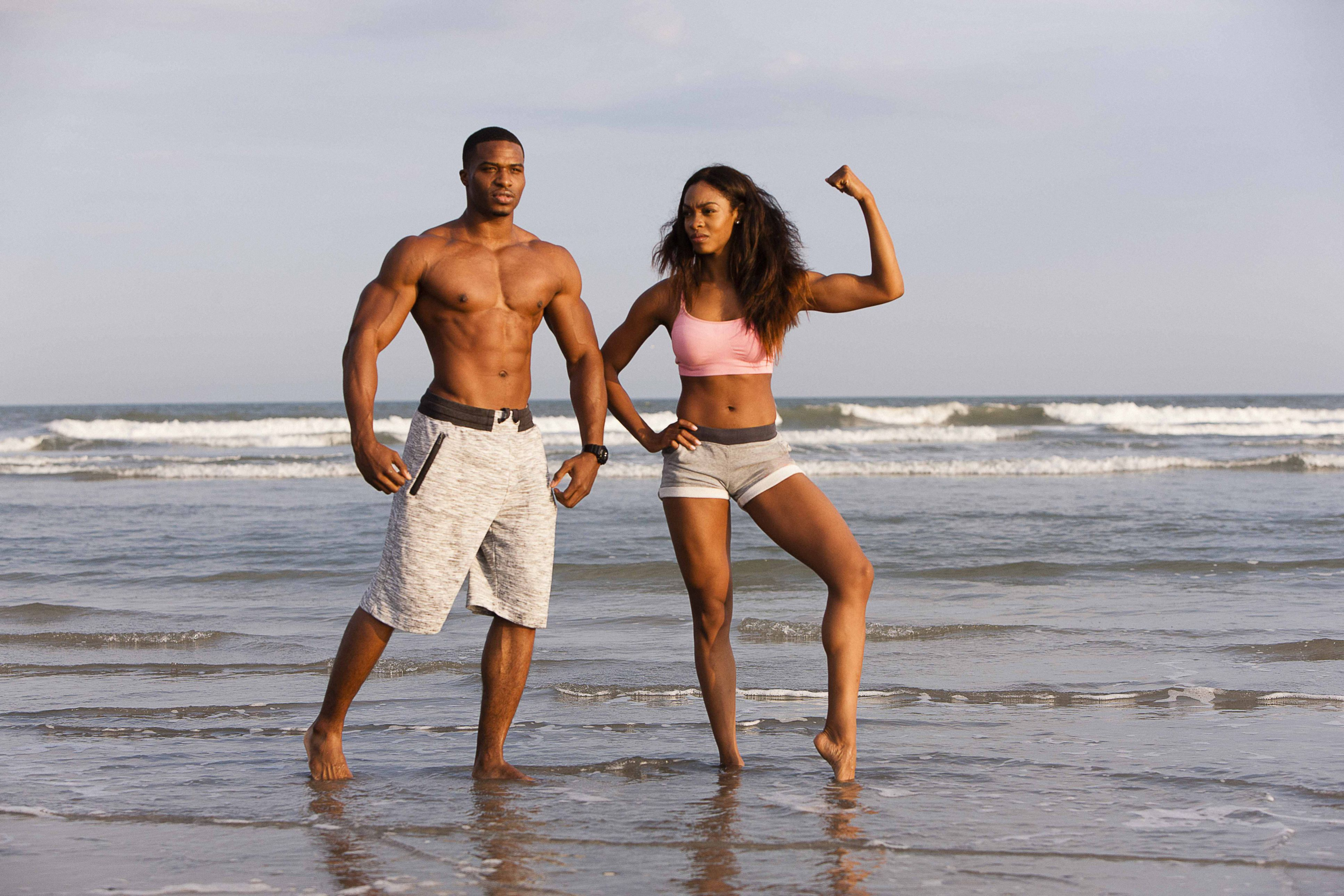 Couple flexing muscles on the beach