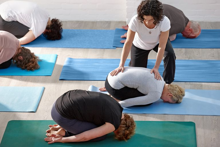 Teacher with hands on a student's back in yoga class