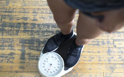 Low section of man checking weight on scale in gym