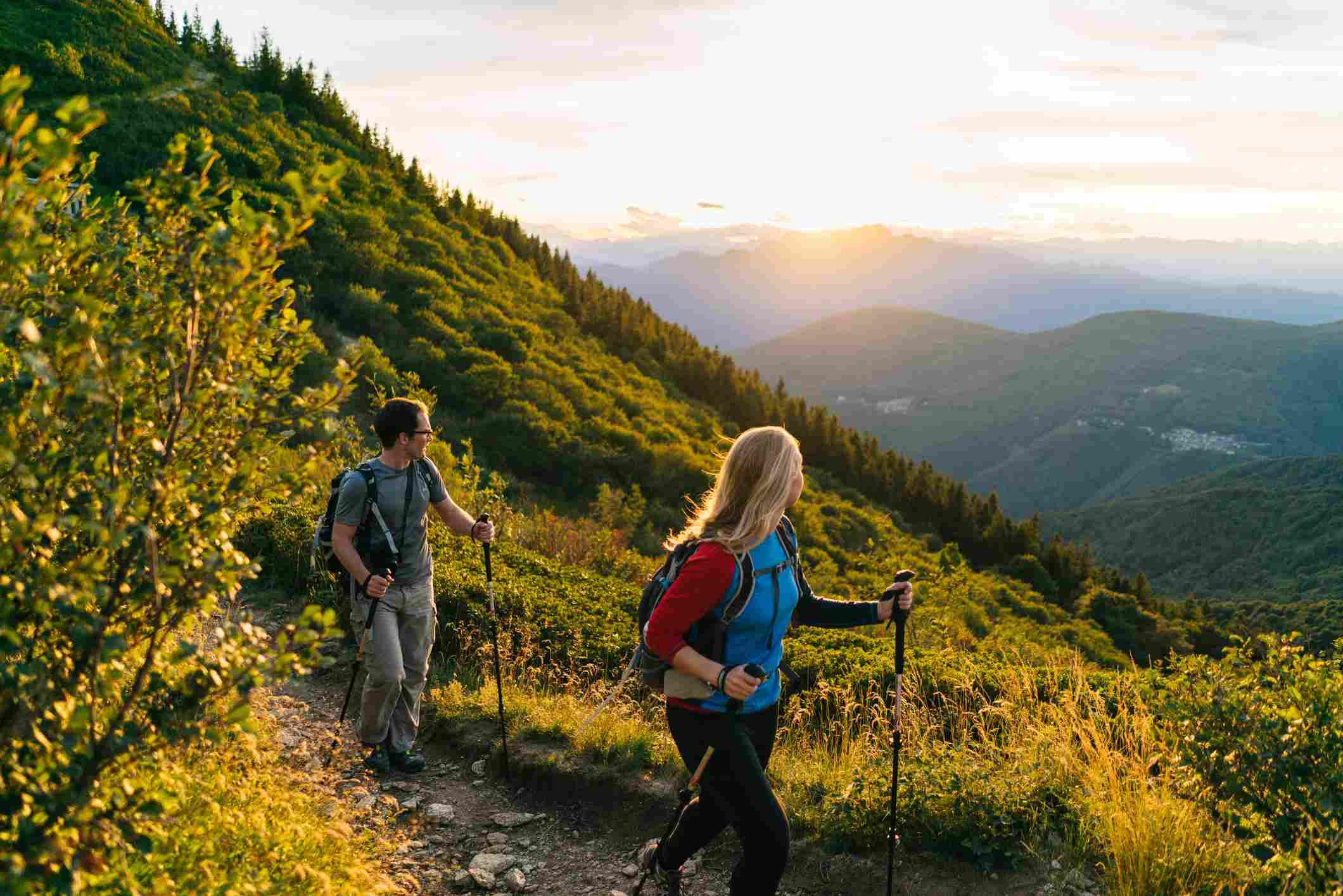 Par de caminatas por un sendero de montaña al amanecer.