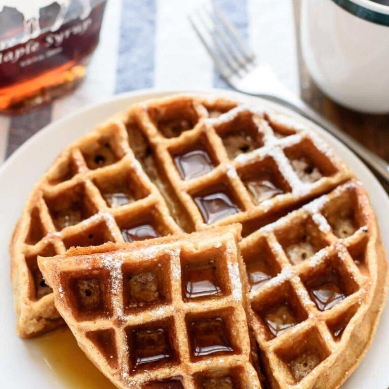 A whole wheat waffle with maple syrup on a plate