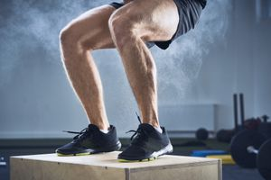 Closeup of man doing box jump exercise at gym