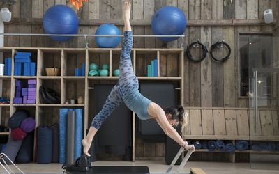 Woman is stretching on a reformer in pilates studio.