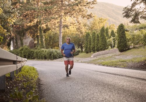 one young overweight man, outdoors nature, running on asphalt road